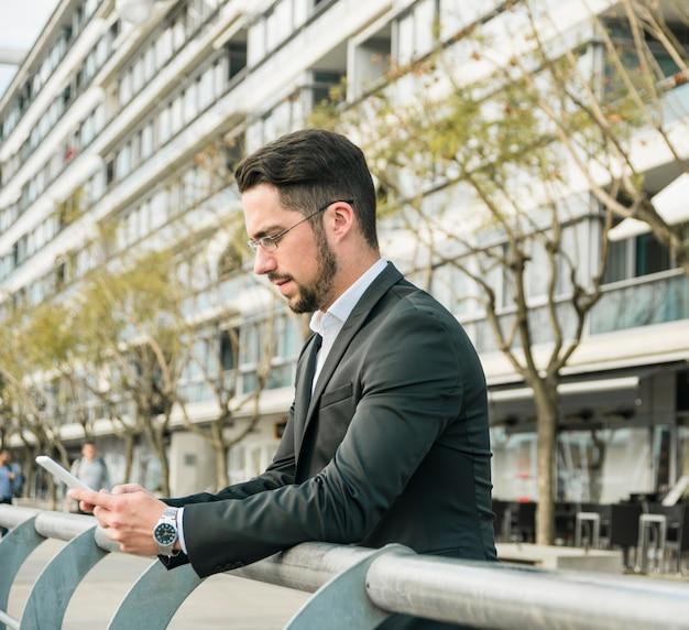 Elegante jovem empresário em pé perto da grade usando telefone celular