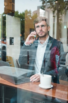 Elegante jovem empresário falando no celular no café