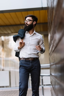 Elegante jovem empresário segurando o casaco por cima do ombro na mão, olhando para longe