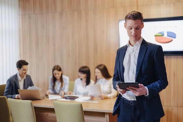 Elegante jovem empresário vestindo uma jaqueta e uma camisa no fundo de um escritório de trabalho com pessoas que trabalham com um tablet
