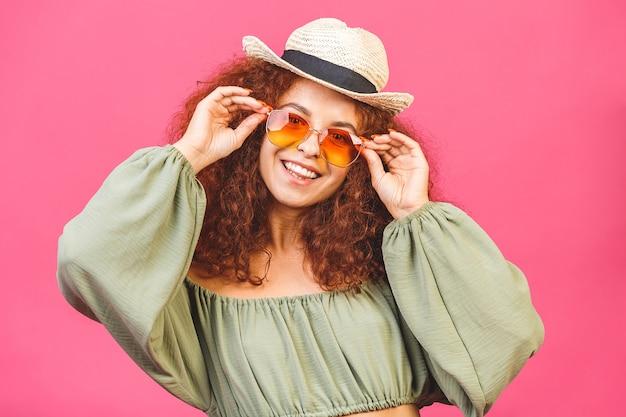 Elegante jovem encaracolada ou mulher com um chapéu de palha e óculos de sol isolados sobre um fundo rosa