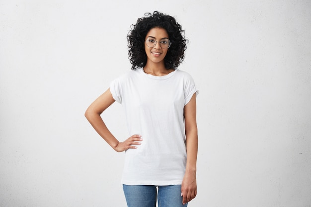 Elegante jovem fêmea de pele escura com cabelos cacheados, olhando e sorrindo fofamente, posando com a mão na cintura dela, isolado