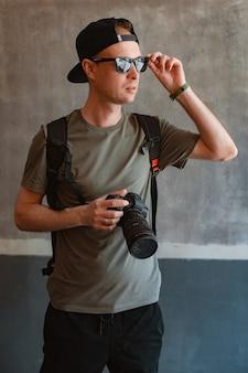 Elegante jovem fotógrafo masculino casualmente vestido com boné preto usando óculos escuros segura uma câmera e um tripé no contexto de uma parede de concreto urbana. conceito de fotógrafo