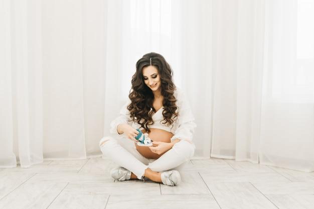 Elegante jovem grávida em roupas brancas com cachos e botas.
