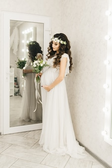 Elegante jovem grávida em roupas brancas com cachos e flores.