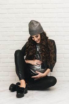 Elegante jovem grávida em roupas pretas com cachos em branco