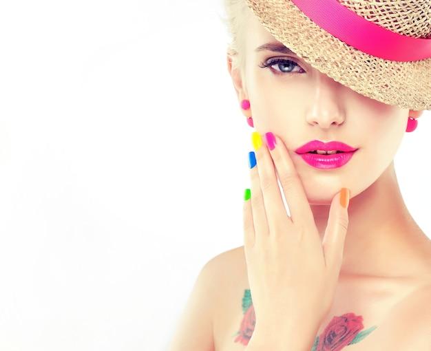 Elegante jovem loira de cabelos, vestida com um chapéu de palha com fita rosa, está demonstrando maquiagem brilhante na moda e esmaltes multicoloridos nas unhas. moda, manicure e cosméticos.