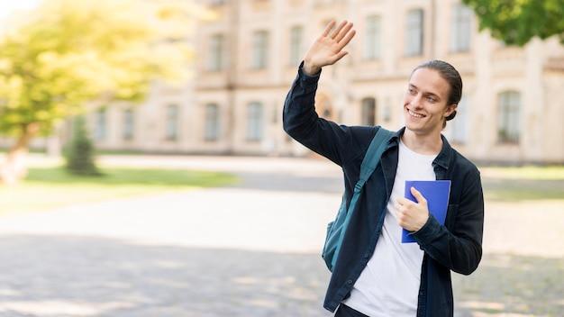 Elegante jovem macho feliz por estar de volta à universidade