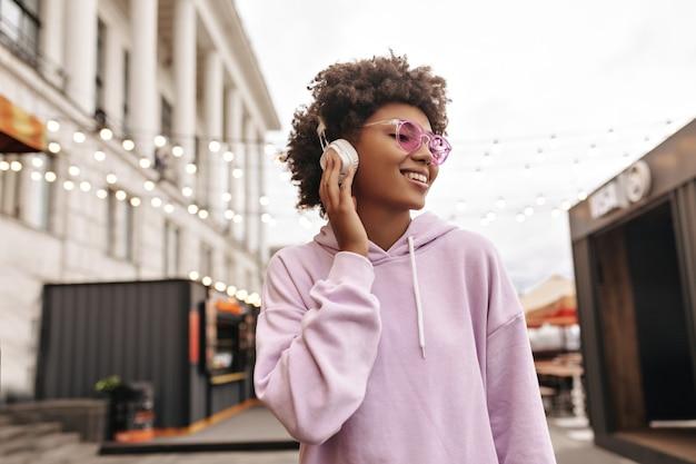 Elegante jovem morena encaracolada com óculos de sol rosa e capuz roxo gosta de música em fones de ouvido e sorri lá fora
