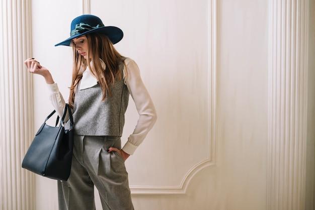 Elegante jovem mulher em traje e chapéu com bolsa no quarto