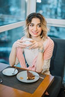 Elegante jovem mulher positiva com copo de bebida perto de smartphone e sobremesa na mesa no café