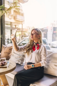 Elegante jovem mulher sentada no café tomando selfie de telefone inteligente