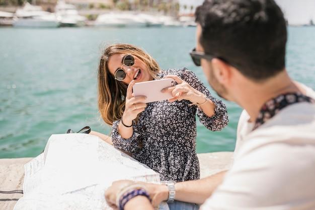 Elegante jovem mulher tirando foto do namorado no cais