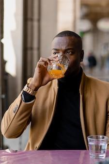 Elegante jovem negro com cara séria, olhando para longe, segurando um copo com suco enquanto está sentado em um café. vida urbana. tiro vertical