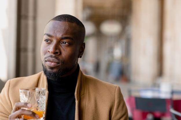 Elegante jovem negro com cara séria, olhando para longe, segurando um copo com suco enquanto está sentado em um café. vida urbana.