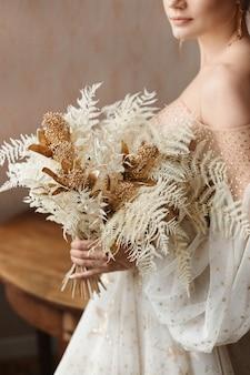 Elegante jovem noiva em elegante vestido vintage posando com elegante bouquet de noiva no interior.