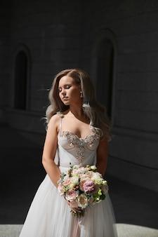 Elegante jovem noiva em vestido de casamento clássico posando com um buquê de noiva modelo feminino ao ar livre em ...