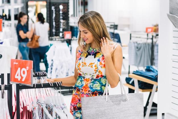 Elegante jovem olhando o vestido pendurado na prateleira no showroom