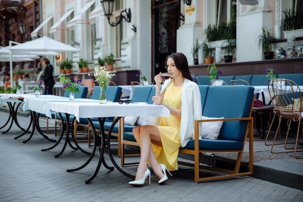 Elegante jovem ou adolescente com uma xícara de café no terraço do café de rua da cidade. menina em um vestido amarelo e jaqueta branca.