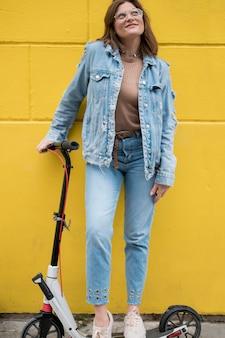Elegante jovem posando com scooter elétrica