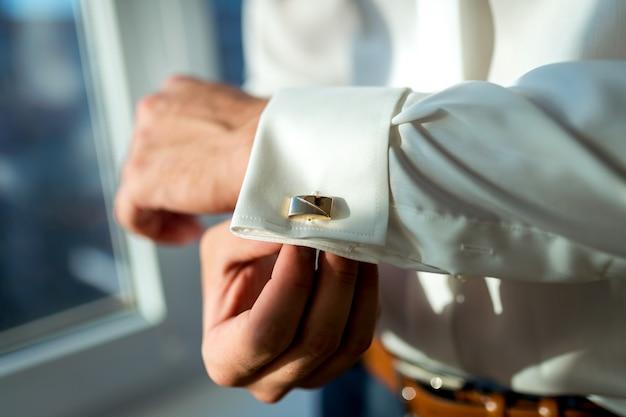 Elegante jovem se preparando para o casamento, close-up do homem mão vestindo camisa branca e botão de punho