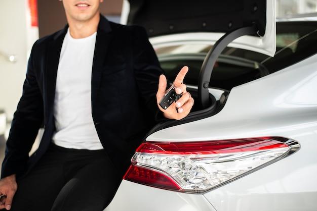 Elegante jovem segurando as chaves do carro