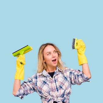 Elegante jovem segurando e olhando para equipamentos de limpeza com a boca aberta