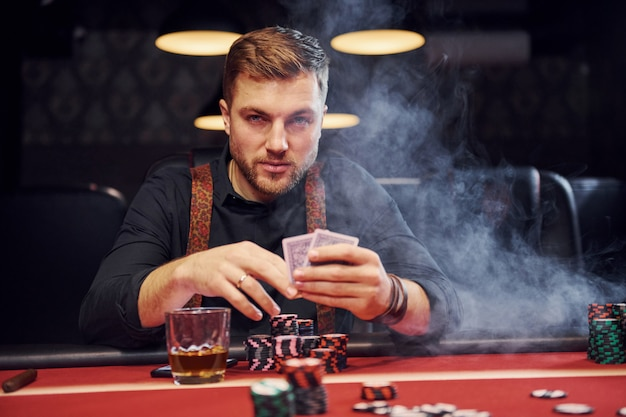 Elegante jovem senta-se no cassino com fumaça nele e joga jogo de pôquer