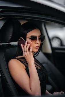 Elegante jovem sentado em um carro de classe executiva em um vestido preto e falando ao telefone. moda e estilo de negócios