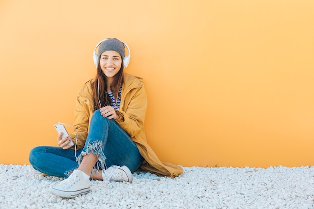 Elegante jovem usando telefone celular usando fones de ouvido, sentado no tapete