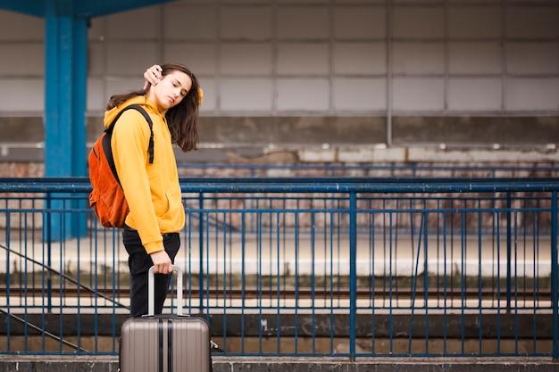 Elegante jovem viajante na estação ferroviária