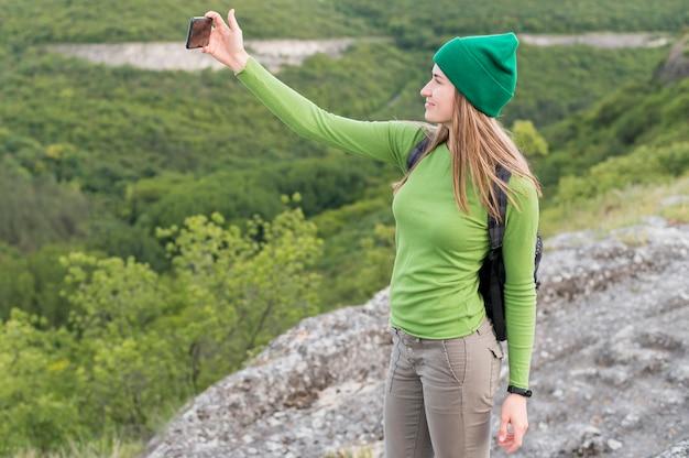 Elegante jovem viajante tomando uma selfie