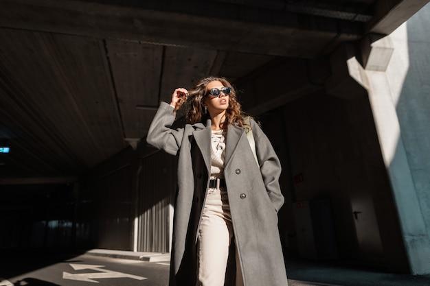 Elegante linda jovem com cabelo encaracolado com óculos de sol com um casaco longo na moda caminha na cidade. modelo feminino, estilo urbano e beleza. luz solar e sombra