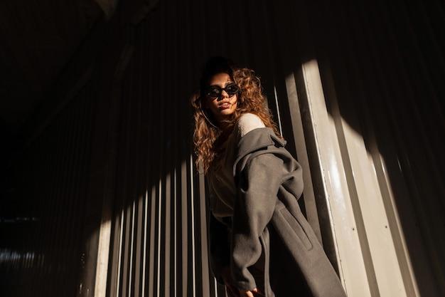 Elegante linda jovem com cabelo encaracolado e óculos escuros legais, vestindo um casaco de outono da moda e suéter de tricô em um meio urbano ao pôr do sol