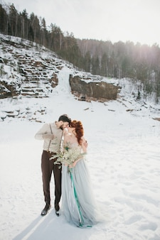 Elegante lindo casal de noivos abraçando. floresta e montanhas de inverno do fundo