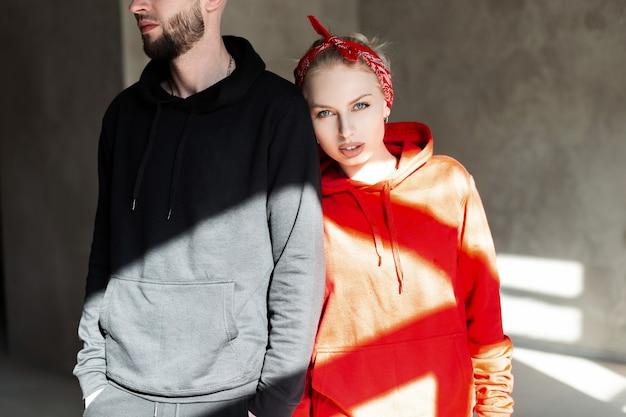 Elegante lindo casal na moda com capuz preto e vermelho da moda dentro de casa com luz solar