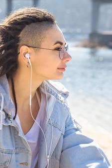 Elegante menina caucasiana ouvindo música com fones de ouvido e descansando na natureza na primavera