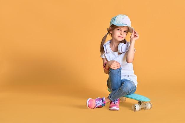 Elegante menina criança menina casual com skate sobre amarelo.