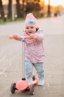 Elegante menina sorri e monta uma scooter no parque ao pôr do sol