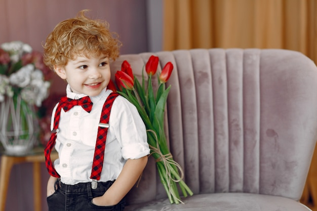 Elegante menino bonitinho com buquê de tulipa