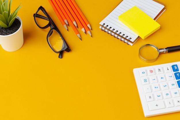 Elegante mesa bagunçada amarela com vários artigos de papelaria vista superior
