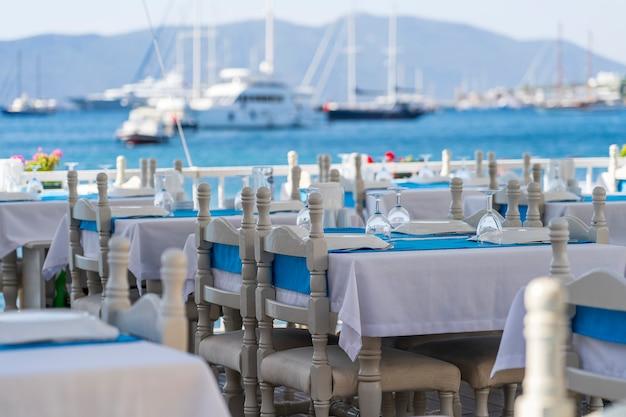 Elegante mesa com garfo, faca, taça de vinho, prato branco e guardanapo azul em restaurante