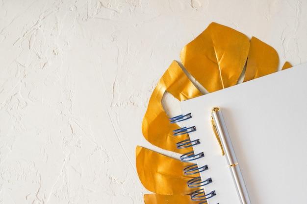 Elegante mock-se composição com folha de ouro monstera, caderno vazio e uma caneta. copie o espaço para texto