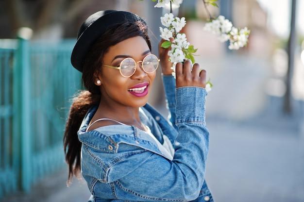 Elegante modelo afro-americano no chapéu de óculos, jaqueta jeans e saia preta posou ao ar livre com árvores de flor na primavera.