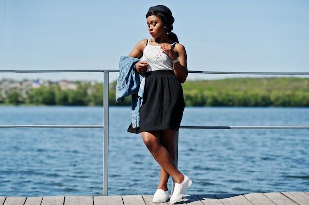 Elegante modelo afro-americano no chapéu de óculos, jaqueta jeans e saia preta posou ao ar livre no cais contra o lago.