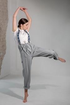 Elegante modelo feminino dançando no estúdio em elegante camisa branca e suspensórios. novo conceito de feminilidade