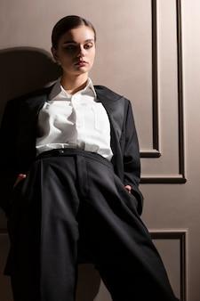 Elegante modelo feminino posando no estúdio em paletó. novo conceito de feminilidade