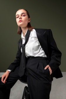 Elegante modelo feminino sentado em uma poltrona em um paletó. novo conceito de feminilidade