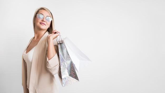 Elegante mulher adulta posando com sacola de compras