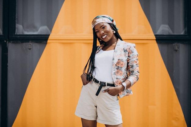 Elegante mulher afro-americana pela parede colorida